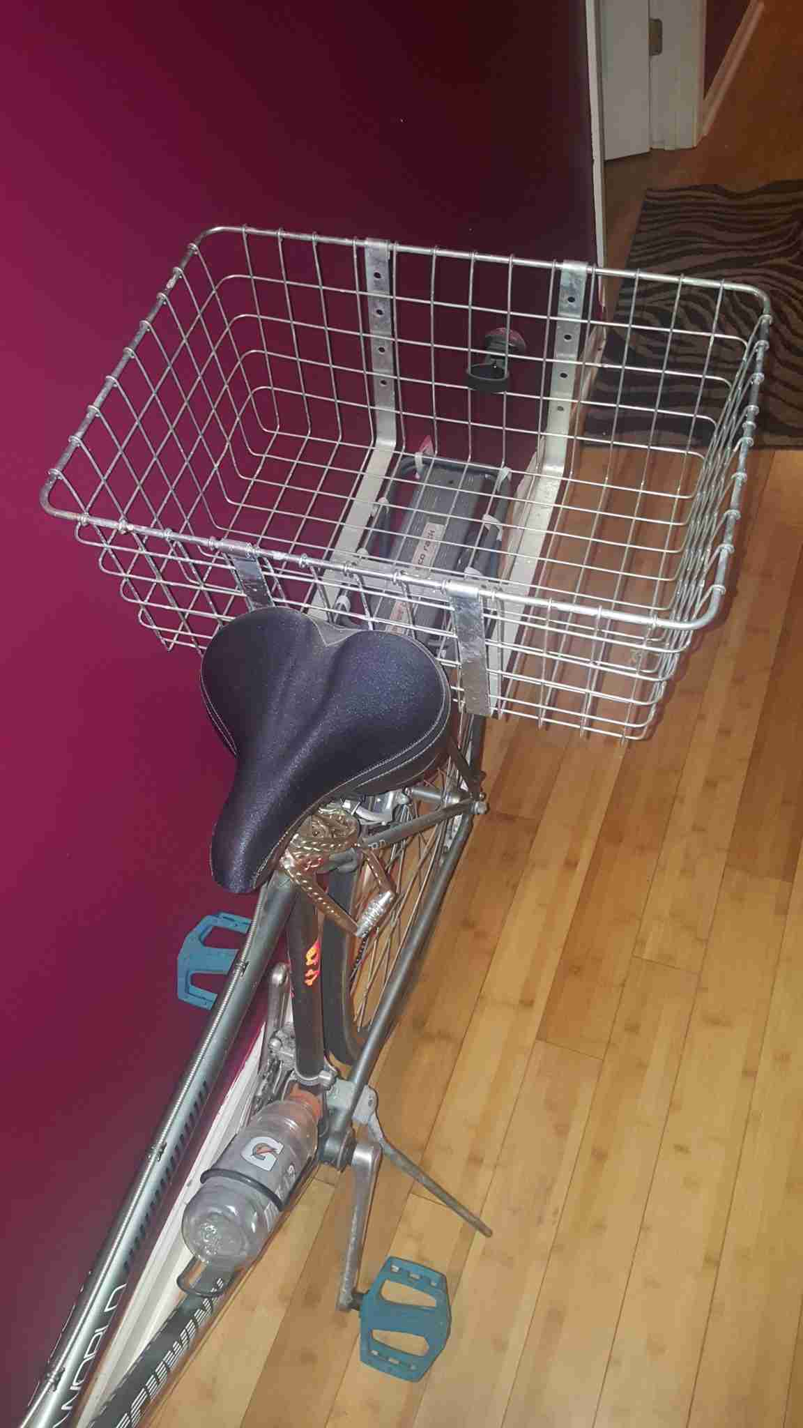I've seen quite a few different methods of toting stuff along with you as you go from place to place, pedaling, ducking, dodging, and darting through traffic, weaving in and out of lunatic drivers. In my brief (and unfortunate) days as a bike courier, I made the investment of getting a metal bike basket attached to the back of my bike. This was not my first attempt to carry a lot of stuff with me without having the added struggle of trying to maintain my balance with a heavy backpack on my own back (I found it quite difficult to turn around to view traffic, to lean into turns, and other very necessary movements that not only keep you safe, but improve the speed and quality of your bike ride.) One of the things I tried before the metal basket on the rear end of my bike was a woven basket.